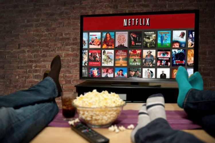 Televisão com catalogo da Netflix aberto na tela, três pessoas com os pés em cima da mesa comendo pipoca